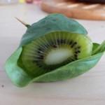 Timide kiwi caché dans sa feuille de basilic